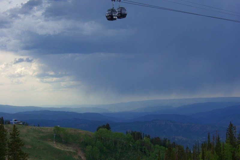 Two gondola cars pass each other above Aspen Mtn ski area, amidst stormy skies.